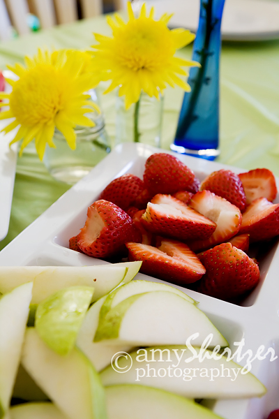 yellow flowers add even more color to a plate of pears and strawberries
