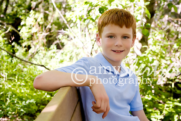 Red headed boy relaxes on a bench in the woods 66742a6e1