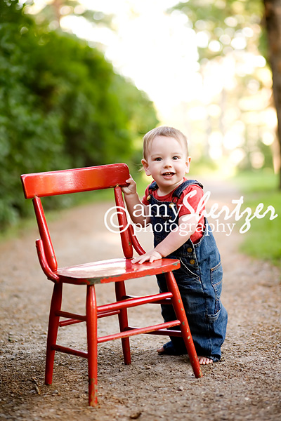 Adorable 1 year old stands by a red chair · Blue-eyed Bozeman Baby boy 0abb0d51b