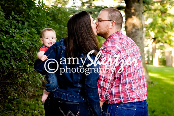 Mom and Dad share a kiss while baby smiles at the camera 8968331c0