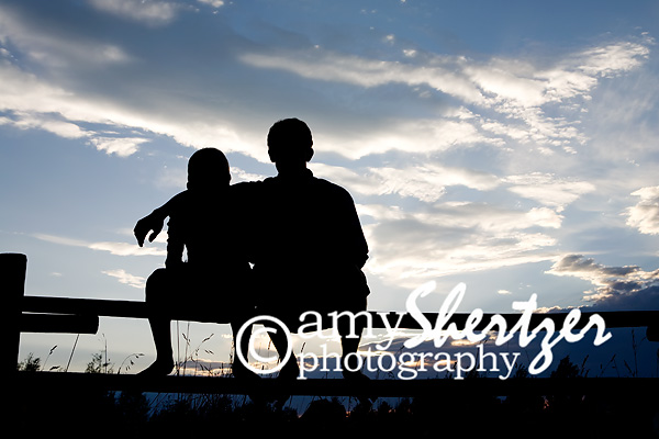 Brothers sit on a split rail fence, silhouetted against a beautiful Montana sky