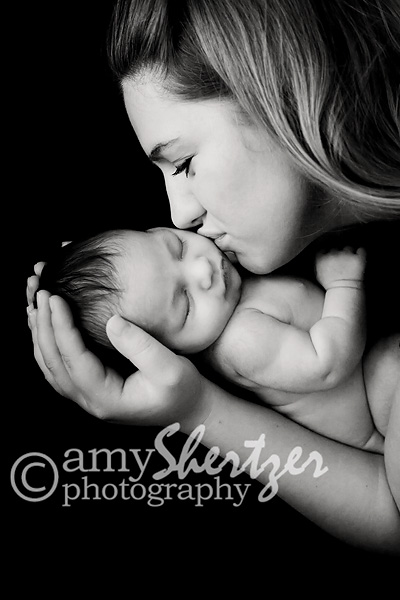 Parents adore their newborn baby. A mother gives a gentle kiss to her new  daughter dc71b0cd6