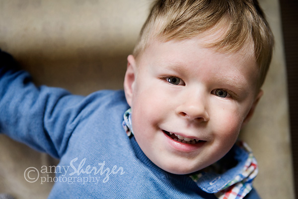 A blue-eyed 4-year-old smiles for a photograph.
