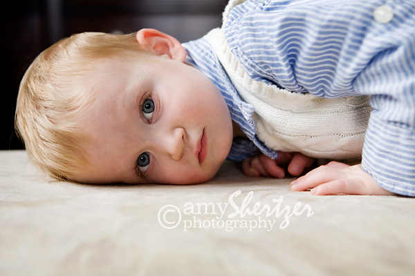 A sleepy baby gives a shy look to the photographer