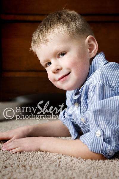 A handsome boy gives a sly smile during a portrait session