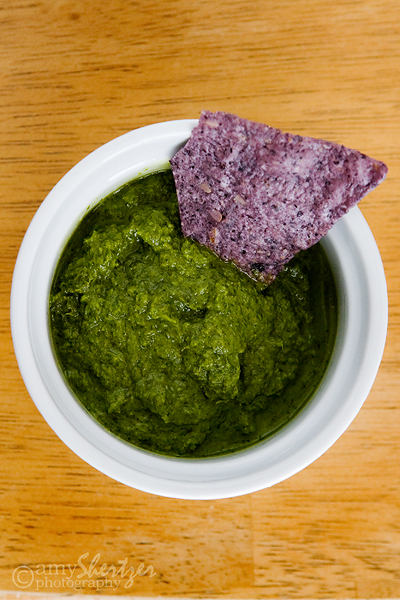 A colorful bowl of green salsa is perfect with blue corn chips.
