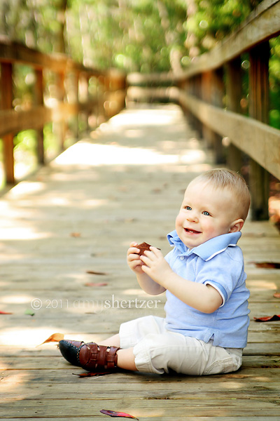 A baby smiles on a boardwalk at the park.
