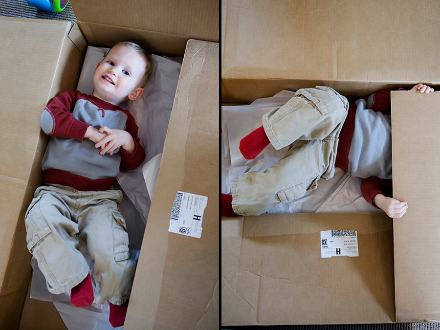 A toddler has fun playing in a large cardboard box.