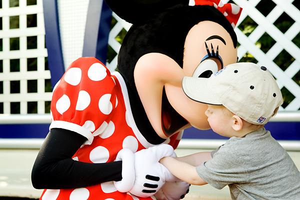 Minnie Mouse gives a kiss to a toddler.