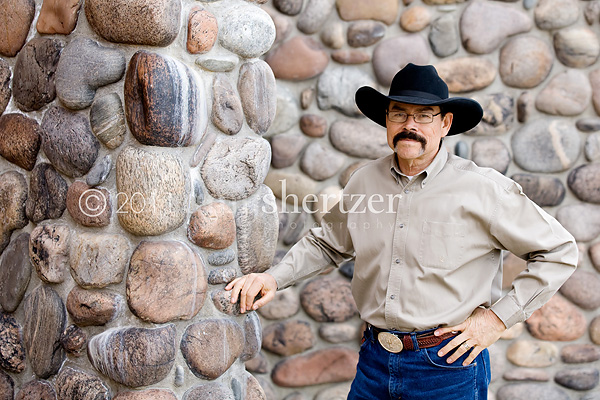 A Bozeman professional poses for a portrait in front of a rock wall.