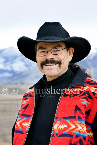 A rancher poses in front of mountains for a professional head shot.