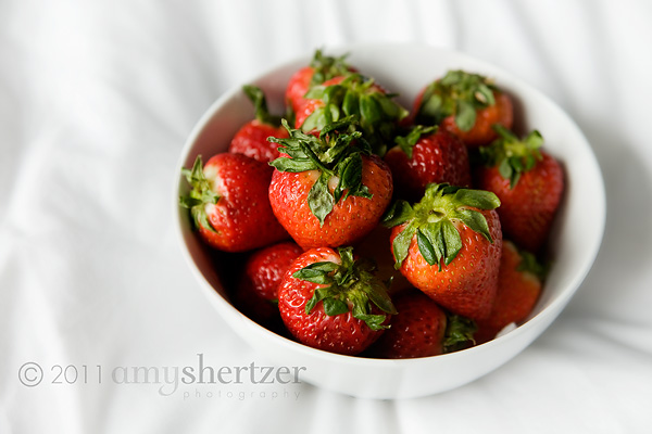 A bowl of red strawberries pops on a white sheet.