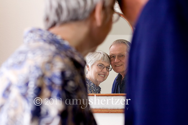 An elderly couple looks into a mirror together.