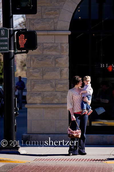 A mother and her son wait on the corner in order to cross the street.