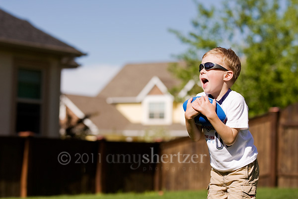 A boy plays catch in his backyard on a sunny summer day in Bozeman, Montana.