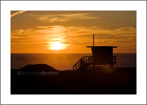A lifeguard stand on a Los Angeles beach at sunset.